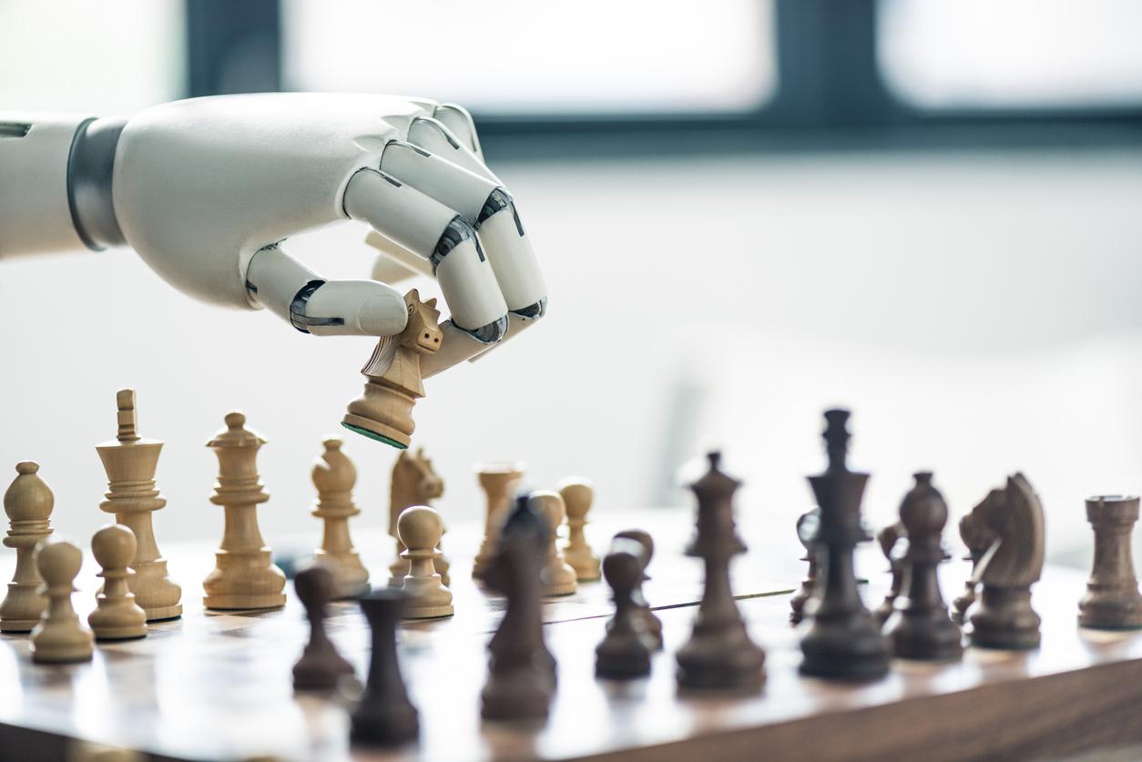 Roboterarm über einem Schachbrett. Der Roboter hält eine Spielfigur in der Hand.